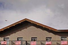 Balcón de madera de la buhardilla de la casa de campo con las banderas americanas fijadas fotografía de archivo libre de regalías