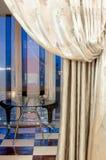 Balcón interior con la tabla de cristal adornada con las cortinas Fotografía de archivo libre de regalías