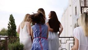 Balcón, terraza La muchacha está retrocediendo de ella en ropa casual elegante Sus amigos funcionados con hasta ella, se divierte almacen de metraje de vídeo