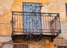 Balcón viejo del cordón del hierro en la casa descolorada del estuco, Grecia Foto de archivo libre de regalías