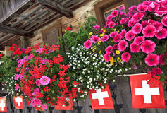 Balcón y banderas en chalet en las montañas suizas Foto de archivo