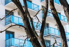 Balcões da construção residencial com as árvores no primeiro plano fotos de stock royalty free