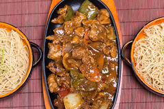 Balck bean sause. Pork in black bean souse with green pepper and onion on the frying pan and noodle in the bowl Royalty Free Stock Images