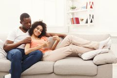 Balck couple making order at food delivery web site, online order. Online order. Happy black couple shopping on tablet at food delivery on sofa at new apartment Stock Photo