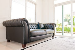 Balck leather on the corner. Black leather couch on the corner with doors and windows Stock Photography