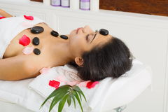 Balck marble stone massage spa for woman at wellness center. Black marble stone hot massage in spa. Female patient in wellness center. Relaxation procedure to Stock Image