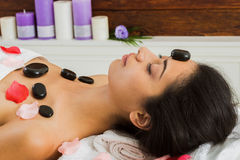 Balck marble stone massage spa for woman at wellness center. Black marble stone hot massage in spa. Female patient in wellness center. Relaxation procedure to Stock Photography