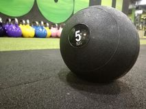 Medicine ball in the gym. Balck medicine ball on the gyms floor. Kattlebells in background stock photos