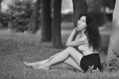 Balck White sexual young woman with long legs and hair in a bright blouse posing in nature Royalty Free Stock Photos