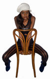 Balck woman sitting in a wooden chair. Isolated on a white background, a beautiful young black woman sits backwards in a old wooden chair with her feet behind royalty free stock images