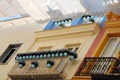 Balcón de la casa con las macetas cubiertas con las toallas en Sevilla Imagen de archivo libre de regalías