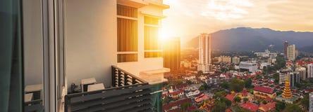 Balcon de condominium avec la vue de fusée de coucher du soleil de la construction de gratte-ciel Images libres de droits