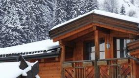 Balcon de cottage sous le fond en bois de forêt de neige de logement de montagne de grenier de chutes de neige banque de vidéos