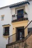 Balcon en fer forgé en métal avec des fleurs, des fenêtres et une icône sur le mur blanc Maison espagnole traditionnelle dans la  image stock