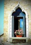balcon fleuri avec une fenêtre dans la maison et beaucoup des pots de fleur photos libres de droits