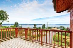 Balcon non meublé et vide avec la vue parfaite de l'eau et les balustrades en bois image stock