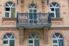 Balcon sur le mur de briques du bâtiment et de beaucoup de fenêtres Photos stock