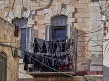 Balcon sur le mur en pierre d'une vieille maison avec un bon nombre de toile noire sur la corde à linge, Jérusalem, Israël Photos libres de droits