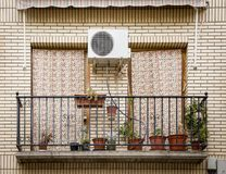 Balcone con i fiori in vasi, in tende ed in una macchina di CA fotografie stock