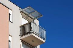 Balcone d'angolo moderno della costruzione di appartamento circondato con la barriera di sicurezza grigia del metallo ed i ciechi fotografia stock