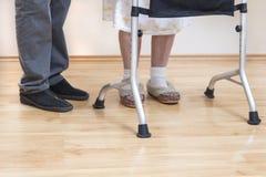 Balconi medici di riabilitazione La nonna impara camminare con l'aiuto di un camminatore ed assistito da un infermiere fotografie stock