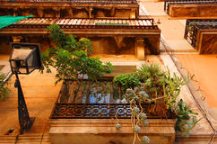 Balconies in Barcelona. Exterior of a multistory building in Barcelona, Spain, showing ornately trimmed balconies with plants hanging and antique light fixtures Stock Photography
