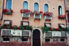 The balconies with red flowers. The sunny Summer in Venice Stock Image