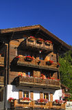 Balconies of a Swiss chalet. Balconies with fiery-red geraniums at a sun-browned Valaisian chalet in the  Valais province of Switzerland Stock Photo