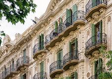 Balconies on th building. Ornamental balconies with green shutters on the old building in Barcelona, Spain Royalty Free Stock Images