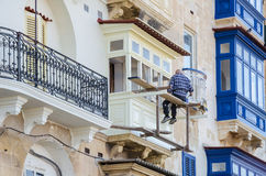 Balconies in Valletta. Valletta, Malta - November 8, 2015: Balconies in Valletta. Man painting his balcony Royalty Free Stock Images