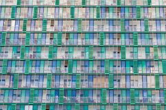 Balconies and windows of a building, apartment houses textured beige green lattices. Stock Images