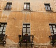 Balconies and Windows. Small balconies and narrow windows overlooking the narrow streets of Cagliari on the island of Sardinia, Italy Stock Image