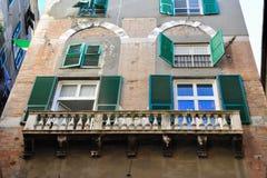 Balcons et fenêtres avec les éclats verts sur la façade du bâtiment à Gênes, Italie images stock