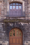 Balcony above door. A balcony above an imposing door in a stone wall Royalty Free Stock Photo