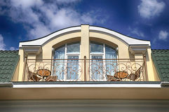 Balcony in attic floor of luxury mansion. Arch window and balcony in attic floor of luxury mansion on summer blue sky background Stock Image