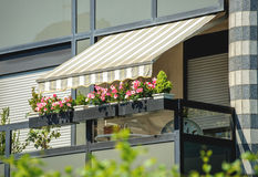 Balcony awning sun protection. Balcony with awning opened and beautiful flowers - covered by sun-shield on a warm summer day royalty free stock photos