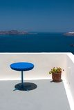 Balcony with blue table and re. View from the balcony to Aegean Sea. Blue table and plant in vase standing on this balcony royalty free stock photo