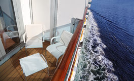 Balcony with chairs and table on ship. Balcony with white chairs and table on ship with view on ship board and deep blue sea Royalty Free Stock Photo