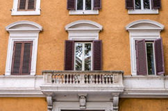 Balcony with columns and windows with shutters with marble ornaments in the old vintage house in Rome, capital of Italy. Balcony with columns and windows with Royalty Free Stock Images