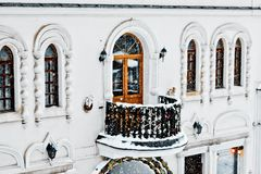 Balcony decorated with Christmas garlands, white building, winter. White building with a balcony decorated with Christmas garlands, white building, winter royalty free stock photography