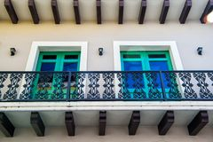 Balcony and two glass windows in San Juan, Puerto Rico. Balcony with decorative metal railing and two glass windows in green frames on plastered wall background stock photography