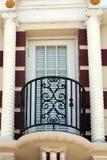 Balcony Doorway with Pillars. White balcony doorway with black wrought iron railing and twisted white pillars stock image