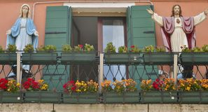 Balcony with figures of Crist and the Virgin. Of a house of Burano, small fisher village in Venice lagoon Stock Photos
