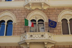 Balcony with flags of Italy and Europe. Ornamental balcony with flags of Italy and Europe on a brown wall Royalty Free Stock Photo