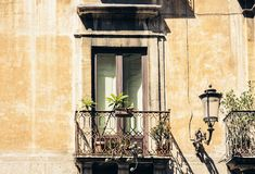 Balcony with flowerpots and house plants in a historic building in Catania, traditional architecture of Sicily, Italy.  stock image