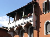 Balcony with flowers in a Garbatella district in Rome. Italy. Bllue clear sky with white clouds. Summer time. Sunny day. Clear red facade. Balcony with columns Stock Photography