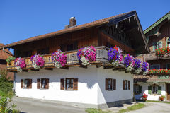 Balcony flowers on a house in Kochel, Bavaria. Balcony Flowers on a old House in Kochel am See, Kochelsee, Farmhouse, Bavaria, Upper Bavaria, Germany, Europe Royalty Free Stock Image