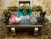 A balcony with flowers and italian flag in Pienza, Italy Royalty Free Stock Photo