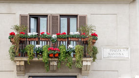 Balcony with flowers on an old yellow apartment building in Rome Royalty Free Stock Photography