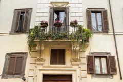 Balcony with flowers  in Rome. Balcony with flowers on an old yellow apartment building in Rome Royalty Free Stock Images